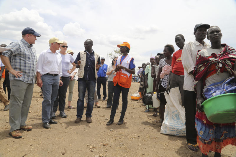 """In this photo taken on Friday April 14, 2017, U.S Senators Chris Coons, left, and Bob Corker, second left, listen to an aid worker as South Sudanese refugees wait for a food distribution at the Bidi Bidi refugee settlement in northern Uganda. In a political climate dominated by President Donald Trump's slogan of """"America First,"""" two U.S. senators are proposing making American food aid more efficient after meeting with victims of South Sudan's famine and civil war. After visiting the world's largest refugee settlement in northern Uganda, Democratic Sen. Chris Coons of Delaware told The Associated Press that the U.S. """"can deliver more food aid at less cost"""" through foreign food aid reform. (AP/Photo/Justin Lynch)"""