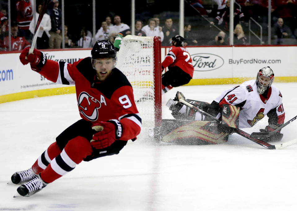 FILE - In this Dec. 21, 2018, file photo, Ottawa Senators goaltender Craig Anderson right, watches as New Jersey Devils left wing Taylor Hall (9) celebrates after scoring a goal during the second period of an NHL hockey game in Newark, N.J. The Devils are doing all they can to make sure Hall re-signs long term rather than leaving in free agency next summer. (AP Photo/Julio Cortez, File)