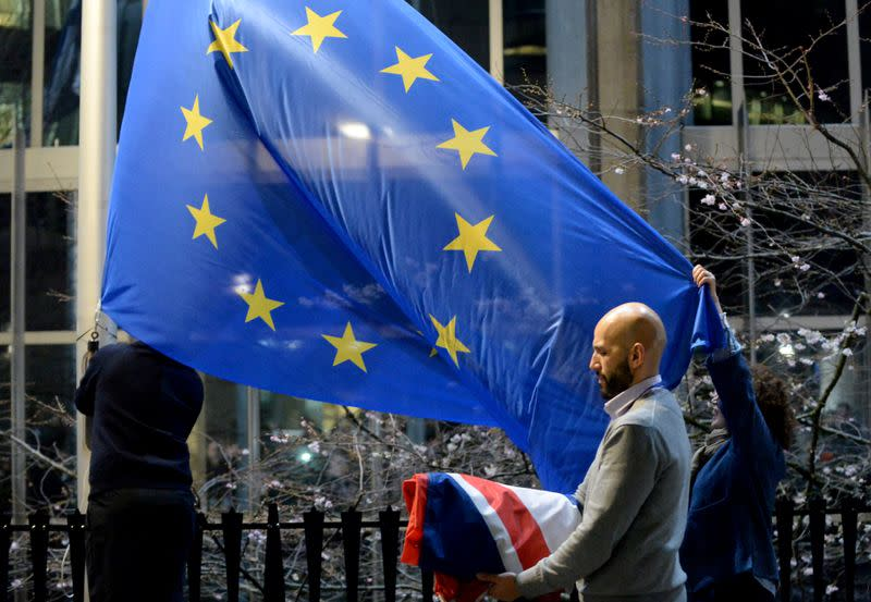 coWorkers replace the British flag outside the European Parliament building with the European Union flag, as Britain leaves the European Union, in Brussels