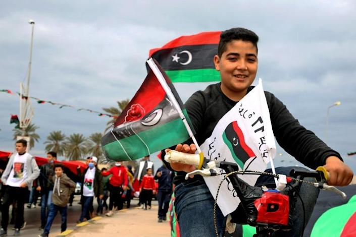 Libyans processed through the capital Tripoli waving the national flag as part of celebrations marking the anniversary of the 2011 NATO-backed uprising that toppled longtime dictator Moamer Kadhafi