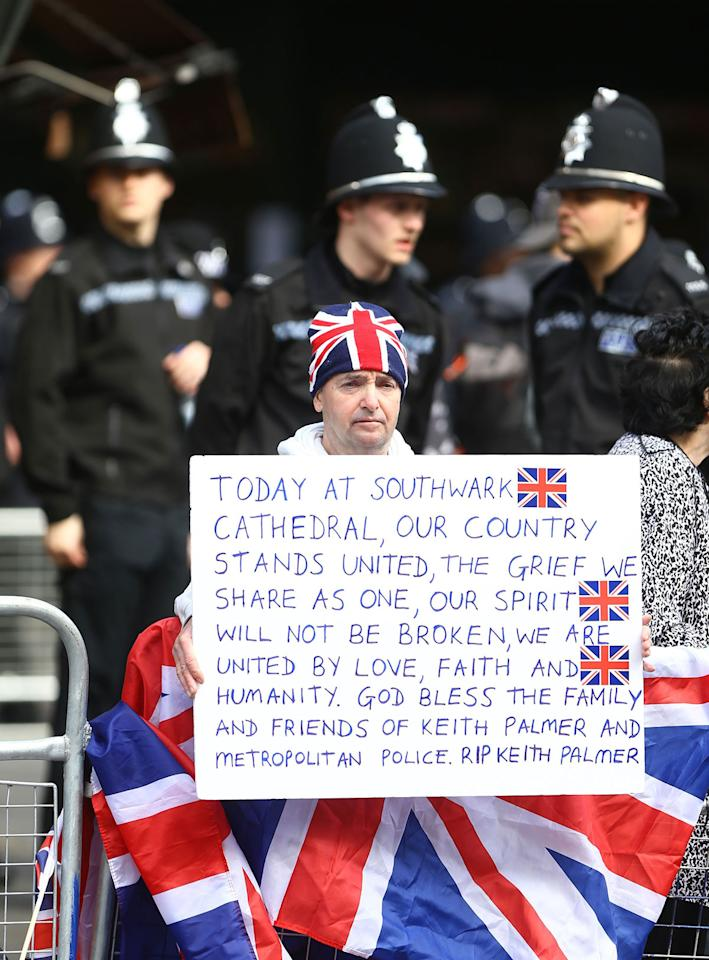 <p>John Loughrey holds a sign outside Southwark Cathedral in London, before the funeral procession of Pc Keith Palmer. (PA Images) </p>