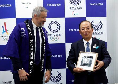 Paris 2024 Director General Etienne Thobois wearing a Japanese happi coat presents a photo of Japanese athletes taken at 1924 Paris Olympic Games to Toshiro Muto, Tokyo 2020 CEO, during a ceremony marking conclusion of MoU between Tokyo 2020 and Paris 2024 Olympic Games in Tokyo, Japan, July 11, 2018. REUTERS/Kim Kyung-Hoon