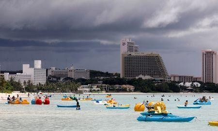 Tourists frolic on the waters overlooking posh hotels in Tumon tourist district on the island of Guam