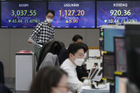 A currency trader walks near screens showing the Korea Composite Stock Price Index (KOSPI), left, and the foreign exchange rate between U.S. dollar and South Korean won, center, at the foreign exchange dealing room of the KEB Hana Bank headquarters in Seoul, South Korea, Thursday, March 4, 2021. Asian shares fell Thursday, tracking a decline on Wall Street as another rise in bond yields rattled investors who worry that higher inflation may prompt central banks to raise ultra-low interest rates. (AP Photo/Ahn Young-joon)
