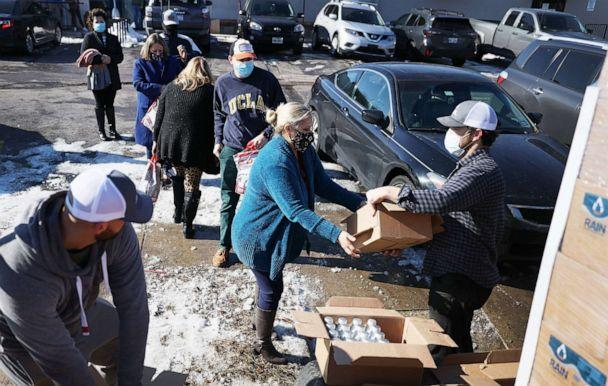 PHOTO: Mark Majkrzak gives out bottles of Rain Pure Mountain Spring Water to people in need on Feb. 19, 2021, in Austin, Texas. Majkrzak, the founder of the company, said he drove from Georgia to deliver water. (Joe Raedle/Getty Images)