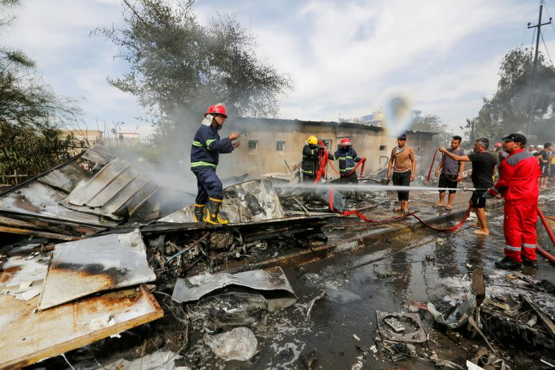 Firefighters inspect the site of a car bomb attack in Sadr City district of Baghdad