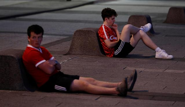 Soccer Football - Liverpool fans watch the Champions League Final - Liverpool, Britain - May 26, 2018 Liverpool fans look dejected after losing the final as they sit beside the river Mersey near Albert Dock REUTERS/Peter Nicholls