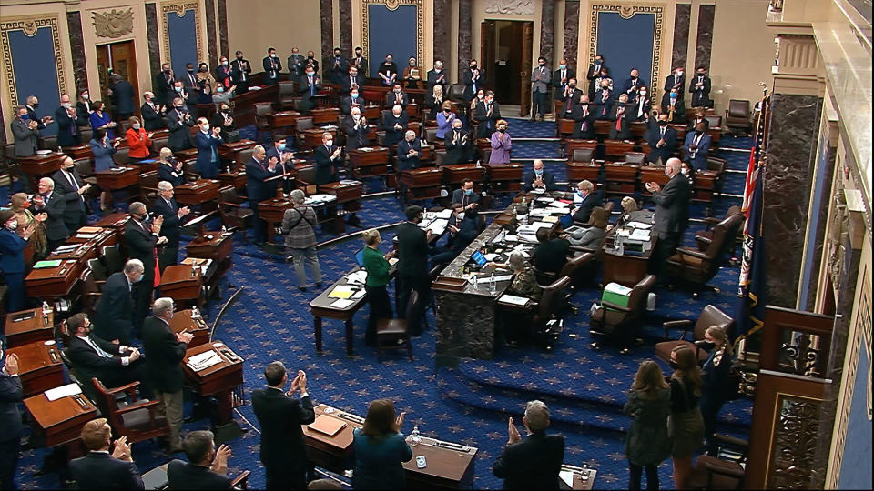 In this image from video, senators stand and applaud support staff, before the final vote on the Senate version of the COVID-19 relief bill in the Senate at the U.S. Capitol in Washington, Saturday, March 6, 2021. (Senate Television via AP)