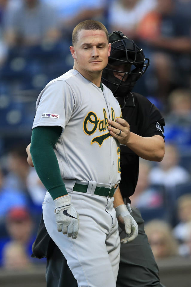 Home plate umpire Chris Segal, back, comes to the aid of Oakland Athletics' Matt Chapman, front, after he was hit by a pitch during the first inning of the team's baseball game against the Kansas City Royals at Kauffman Stadium in Kansas City, Mo., Wednesday, Aug. 28, 2019. (AP Photo/Orlin Wagner)