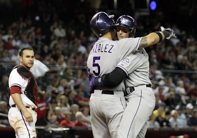 PHOENIX, AZ - APRIL 29: Troy Tulowitzki #2 of the Colorado Rockies celebrates with Carlos Gonzalez #5 after Tulowitzki hit a two run home-run against the Arizona Diamondbacks during the sixth inning of the MLB game at Chase Field on April 29, 2014 in Phoenix, Arizona. (Photo by Christian Petersen/Getty Images)