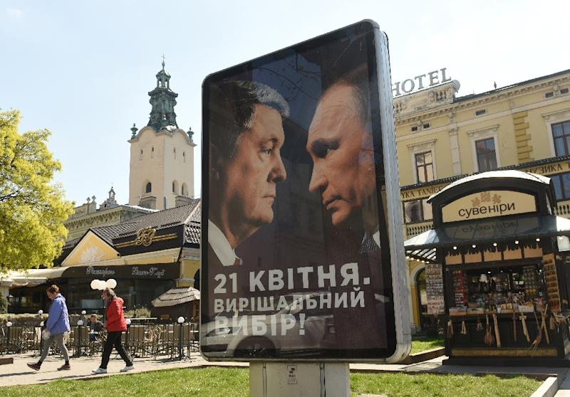 "A campaign billboard reads ""April 21st. Decisive choice!"", bearing the portraits of Ukrainian President Petro Poroshenko and Russian President Vladimir Putin in the center of the western Ukrainian city of Lviv (AFP Photo/Yuri DYACHYSHYN)"