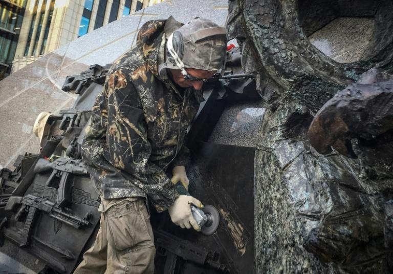 A man uses an angle grinder to obliterate a sketch of a German StG44 rifle from the newly-unveiled monument to Mikhail Kalashnikov, inventor of the Red Army's AK-47 assault rifle, in Moscow on September 22, 2017