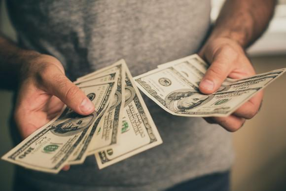 A man holds several hundred dollar bills in his hand.