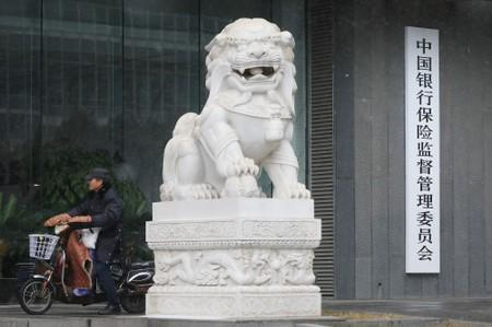 A man rides an electric bike past the CBIRC building in Beijing