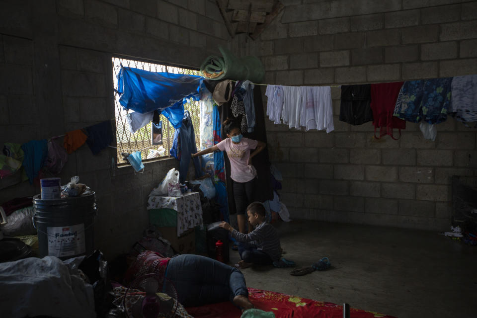 A family left homeless by last year's hurricanes Eta and Iota live inside an empty warehouse near the Chamelecon neighborhood of San Pedro Sula, Honduras, Tuesday, Jan. 12, 2021. The devastation wrought by November's hurricanes and the economic damage of the COVID-19 pandemic has added to the forces of poverty and gang violence that drive Hondurans to migrate. (AP Photo/Moises Castillo)
