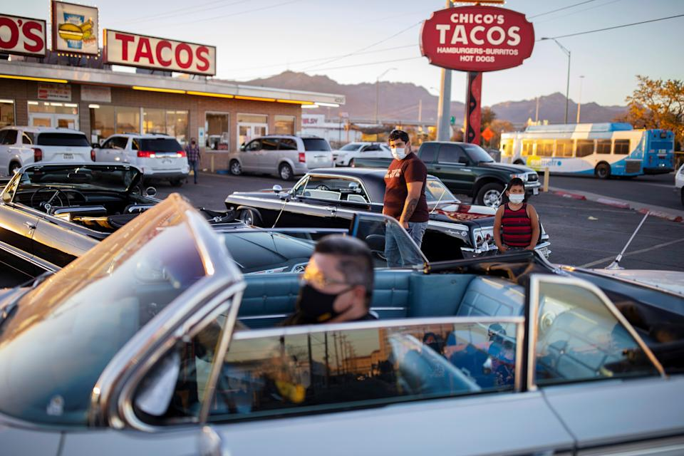 A man parks his low rider car as two boys look on outside one of the city's most popular restaurants amid the coronavirus disease (COVID-19) outbreak, in El Paso, Texas, U.S. November 15, 2020. REUTERS/Ivan Pierre Aguirre