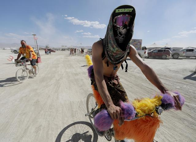 <p>Burning Man participant Bob Rafie of France pedals his bike through Black Rock City as approximately 70,000 people from all over the world gathered for the 1st full days of the annual Burning Man arts and music festival in the Black Rock Desert of Nevada, Aug. 28, 2017. (Photo: Jim Bourg/Reuters) </p>