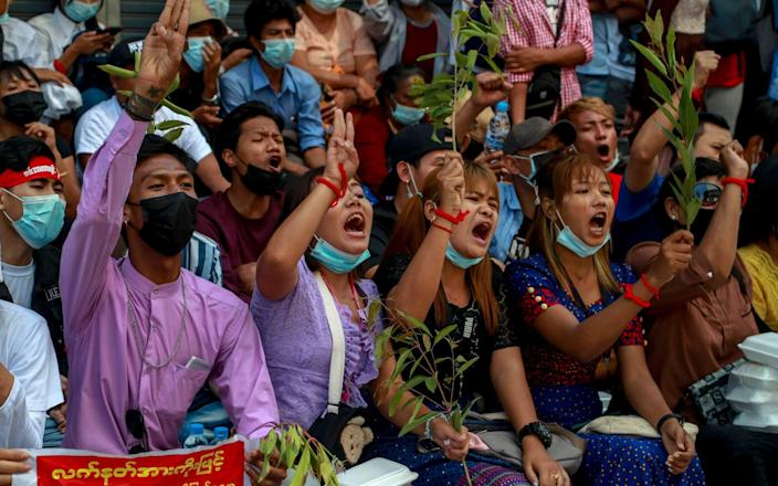 Anti-coup protesters shout slogans in Yangon, Myanmar - AP Photo