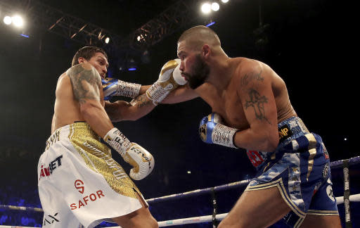 Tony Bellew, right, hits Oleksandr Usyk with a right during their cruiserweight boxing bout Saturday, Nov. 10, 2018, in Manchester, England. Usyk successfully defended his four belts and likely sent Bellew into retirement by knocking out the British fighter in the eighth round. (Nick Potts/PA via AP)
