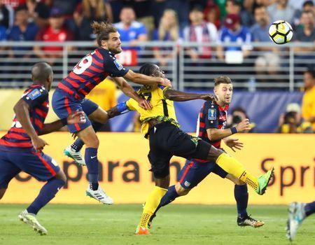 Jul 26, 2017; Santa Clara, CA, USA; United States midfielder Graham Zusi (19) pulls down Jamaica forward Darren Mattocks in the second half during the CONCACAF Gold Cup final at Levi's Stadium. Zusi would receive a yellow card penalty on the play. Mandatory Credit: Mark J. Rebilas-USA TODAY Sports