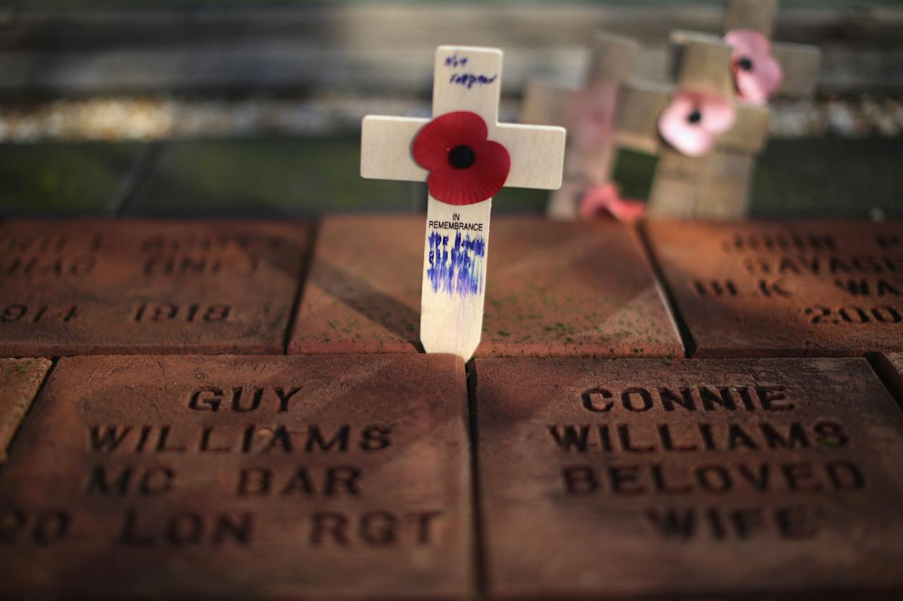 ALREWAS, UNITED KINGDOM - NOVEMBER 11:  A cross and poppy are placed between memorial stones at The National Memorial Arboretum during the remembrance Service on November 11, 2012 in Alrewas, England. The Armed Forces Memorial, is the UK's tribute to the men and women who have been killed on duty or as a result of terrorist action since 1948. Their names are inscribed on the giant Portland stone walls. The obelisk is specifically dedicated to those who have died whilst in service. The Armed Forces Memorial has been designed to allow a shaft of sunlight to fall across the sculpted wreath on the central stone on Armistice Day at precisely 11:00am on the 11th day of the 11th month, the time when fighting formally stopped in World War I.  (Photo by Christopher Furlong/Getty Images)