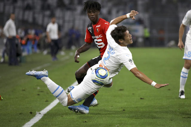 Marseille's Hiroki Sakai falls to the ground while battling for the ball with Rennes' Eduardo Camavinga during the French League One soccer match between Marseille and Rennes at the Velodrome stadium in Marseille, southern France, Sunday, Sept. 29, 2019. (AP Photo/Daniel Cole)