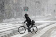 A person rides a bike during a snowfall in Berlin