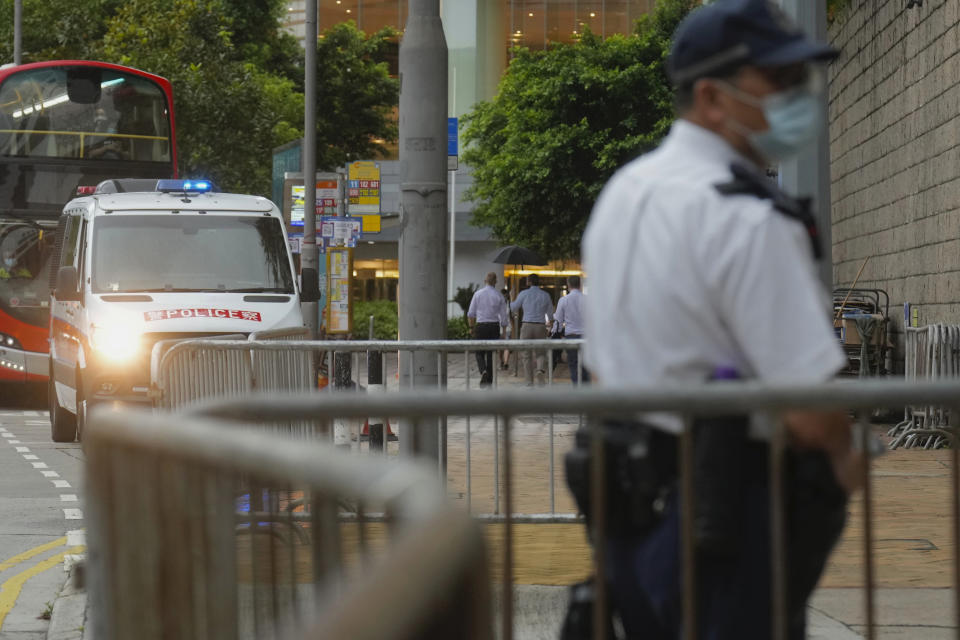 """A police officer stands guard while waiting for Tong Ying-kit's arrival at the Hong Kong High Court in Hong Kong Friday, July 30, 2021. Tong Ying-kit was convicted Tuesday of inciting secession and terrorism for driving his motorcycle into a group of police officers during a July 1, 2020, pro-democracy rally while carrying a flag bearing the banned slogan, """"Liberate Hong Kong, revolution of our times."""" Tong, 24, will be sentenced Friday, the court announced. (AP Photo/Vincent Yu)"""