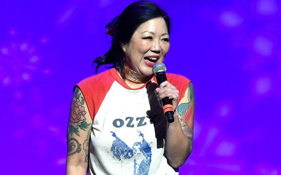Cho performing on stage, with tattoos on display