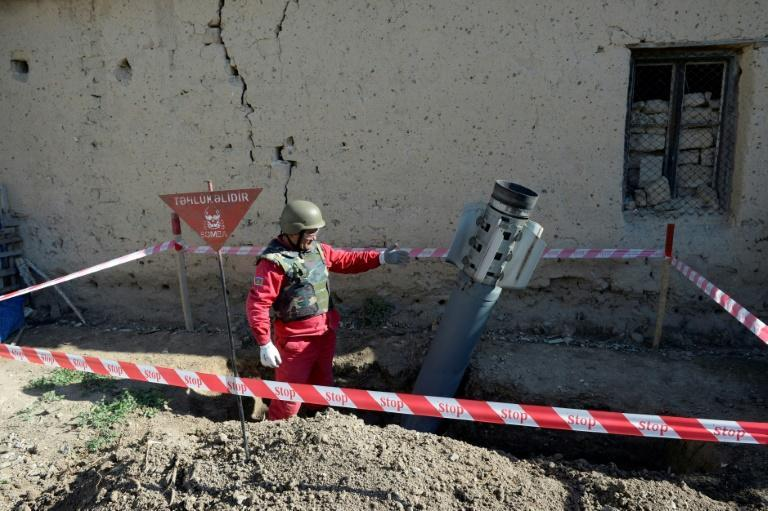 An officer approaches a rocket before defusing it in the village of Tap-Qaragoyunlu in Azerbaijan