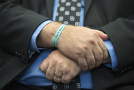 """Tony Montalto, whose 14-year-old daughter Gina was killed in the Parkland school mass shooting and who is president of """"Stand with Parkland,"""" wears a bracelet with Gina's name during the announcement of the release of the Secret Service National Threat Assessment Center's Protecting America's Schools report, in Washington, Thursday, Nov. 7, 2019. The report examines 41-targeted attacks that occurred in schools between 2008 and 2017. (AP Photo/Cliff Owen)"""