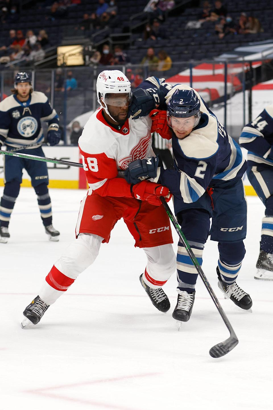 Givani Smith #48 of the Detroit Red Wings and Andrew Peeke #2 of the Columbus Blue Jackets skate after the puck during the first period of the game at Nationwide Arena on May 7, 2021