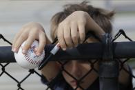 A young fan waits for a player to sign his baseball during a Philadelphia Phillies spring training baseball workout Friday, Feb. 14, 2020, in Clearwater, Fla. Big league managers say that Major League Baseball has instructed them to prepare for spring training to start on time in mid-February despite uncertainty around the coronavirus. Tampa Bay Rays manager Kevin Cash said Wednesday, Dec. 16, 2020, that officials from the commissioner's office had a meeting with managers Tuesday an expressed optimism about opening spring camps as scheduled.(AP Photo/Frank Franklin II)