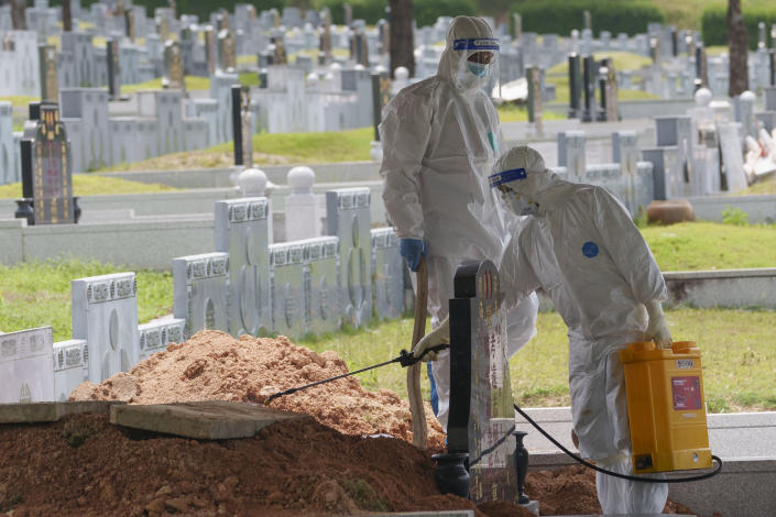 Health workers wearing Personal Protective Equipment (PPE) sanitize during the funeral for a COVID-19 victim at Nirvana memorial, a Buddhist, Taoist and Christian cemetery in Semenyih, Malaysia, Wednesday, May 26, 2021. Malaysia's latest coronavirus surge has been taking a turn for the worse as surging numbers and deaths have caused alarm among health officials, while cemeteries in the capital are dealing with an increasing number of deaths. (AP Photo/Vincent Thian)