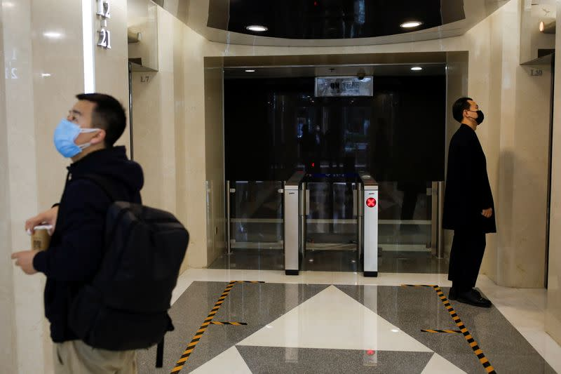 Men wearing face masks stand next to lines serving as a guide for social distancing, while waiting for the elevators at an office building, following an outbreak of the coronavirus disease (COVID-19), in Beijing