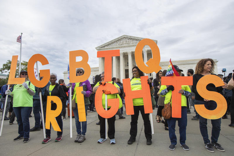 Supporters of LGBTQ rights hold placards in front of the U.S. Supreme Court, Tuesday, Oct. 8, 2019, in Washington. The Supreme Court heard arguments in its first cases on LGBT rights since the retirement of Justice Anthony Kennedy. (AP Photo/Manuel Balce Ceneta)
