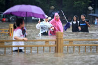 People walk through floodwaters along a street in Zhengzhou in central China's Henan Province, Tuesday, July 20, 2021. China's military has blasted a dam to release floodwaters threatening one of its most heavily populated provinces. The operation late Tuesday night in the city of Luoyang came after several people died in severe flooding in the Henan provincial capital of Zhengzhou, where residents were trapped in the subway system and left stranded at schools, apartments and offices. (Chinatopix via AP)