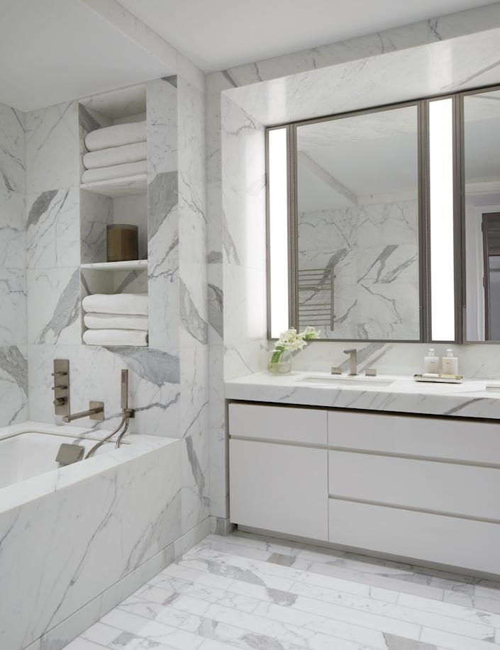 """While Love and team made changes throughout the apartment—replacing floors, adding exposed beams, and much more—they left the bright and minimalist bathroom suite as is. Well, except for one thing. """"We upgraded to a Toto toilet,"""" says Varnum. Adds Love, """"When it comes to accommodations for tall people, you find the most discrepancies in the bathroom. We had to make sure the rain-shower shower head was just right. You know, NBA height."""""""