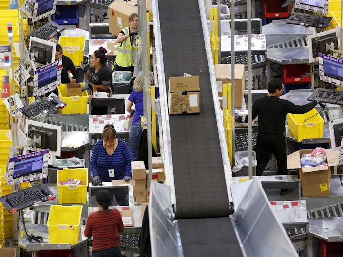 Workers prepare orders for customers at the Amazon Fulfillment Center in Tracy, California, November 29, 2015.
