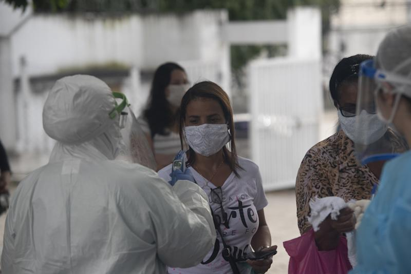 RIO DE JANEIRO, BRAZIL â MAY 14 : A health official takes temparature of people at field hospital for testing coronavirus (Covid-19) in Rio de Janeiro, Brazil on May 14, 2020. (Photo by Fabio Teixeira/Anadolu Agency via Getty Images)