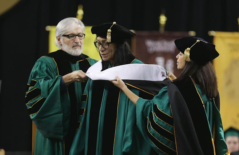 """Wayne State University Board of Governors Paul Massaron, left, and Sandra Hughes O'Brien confer a Doctor of Humane Letters honorary degree to Sixto Rodriguez, Thursday, May 9, 2013 in Detroit, during the university's commencement. Rodriguez's two albums in the early 1970s received little attention in the United States but he unknowingly developed a cult following in South Africa during the apartheid era. He was the subject of an Oscar-winning documentary, """"Searching for Sugar Man."""".(AP Photo/Carlos Osorio)"""