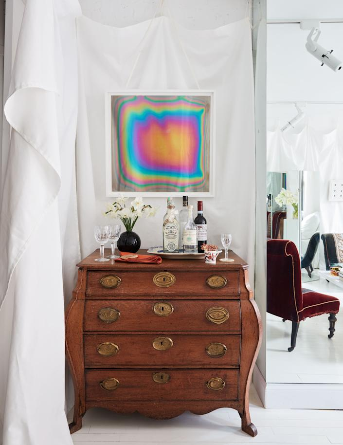 A framed artwork by Aleksandar Duravcevic hangs above the 18th-century chest.