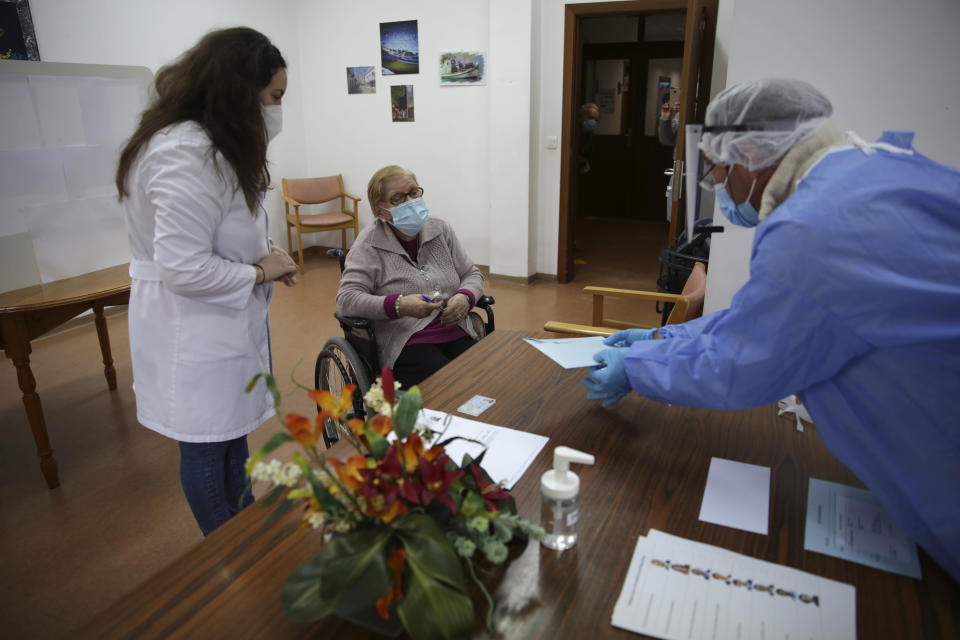 Olivia Bibe, 87, watches as municipal worker Mario Matos, right, seals an envelope with her presidential election ballot at the elderly care home where she resides in Montijo, south of Lisbon, Tuesday, Jan. 19, 2021. For 48 hours from Tuesday, local council crews are collecting the votes from people in home quarantine and from residents of elderly care homes ahead of Sunday's presidential election. (AP Photo/Armando Franca)