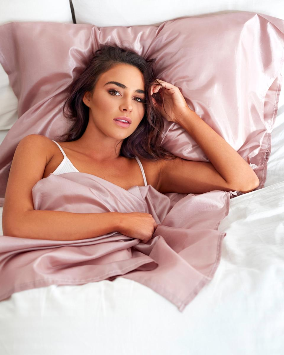 A tanned woman lying in a Tanzee bedsheet protector in bed