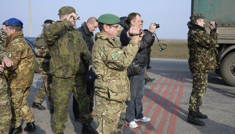 OSCE military observers take photos during negotiations with pro-Russian soldier forces at the Chongar check point blocking the entrance to Crimea on March 7, 2014