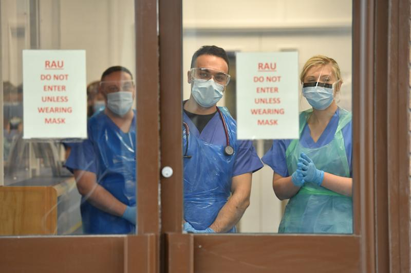 Medical staff wearing personal protective equipment (PPE) wait to receive coronavirus patients at the door of the Respiratory Assessment Unit at the Morriston Hospital in Swansea, as the health services prepare their response to the coronavirus outbreak.