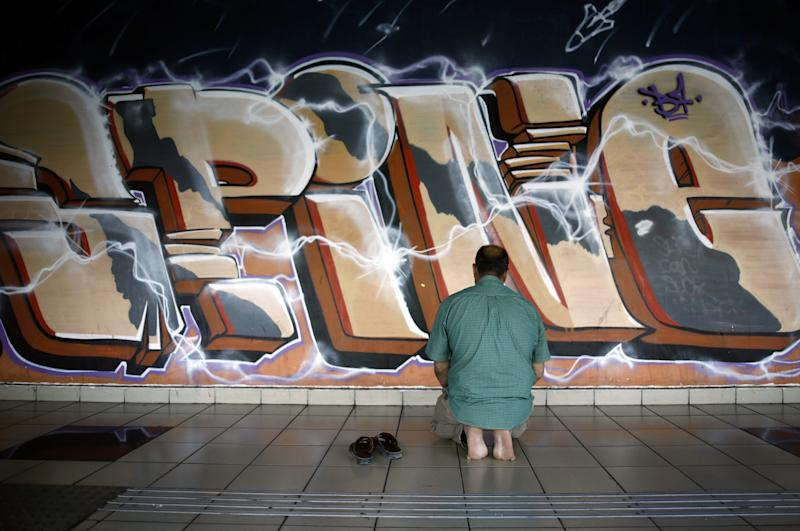 A Muslim man prays near graffiti at the Central Bus Station on May 29. (Photo: Corinna Kern/Reuters)