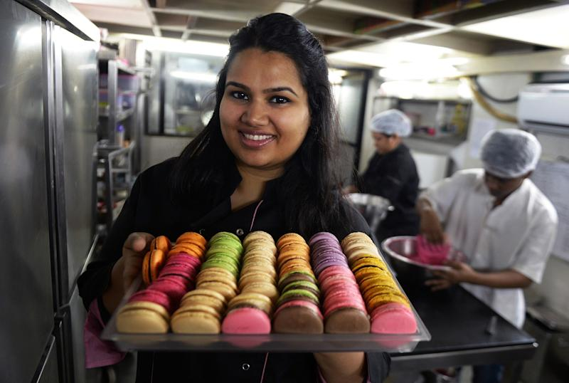 Pooja Dhingra poses holding a tray of macarons at the Le15 - Patisserie bakery in Mumbai. (Photo by PUNIT PARANJPE/AFP via Getty Images)