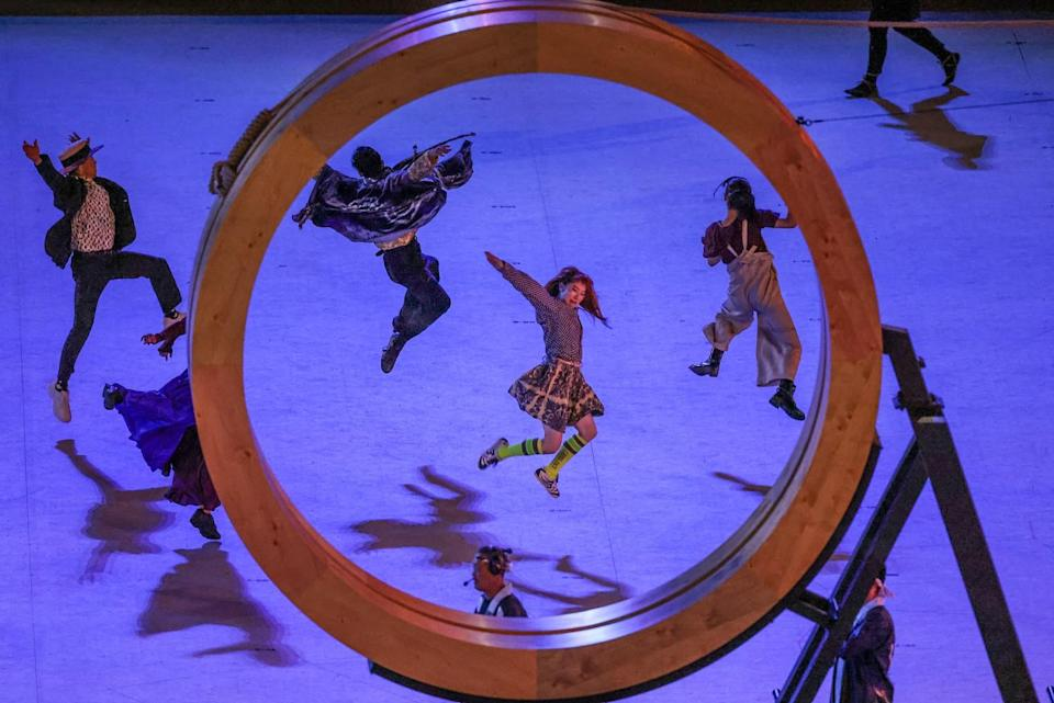 Dancers are framed inside an Olympic ring