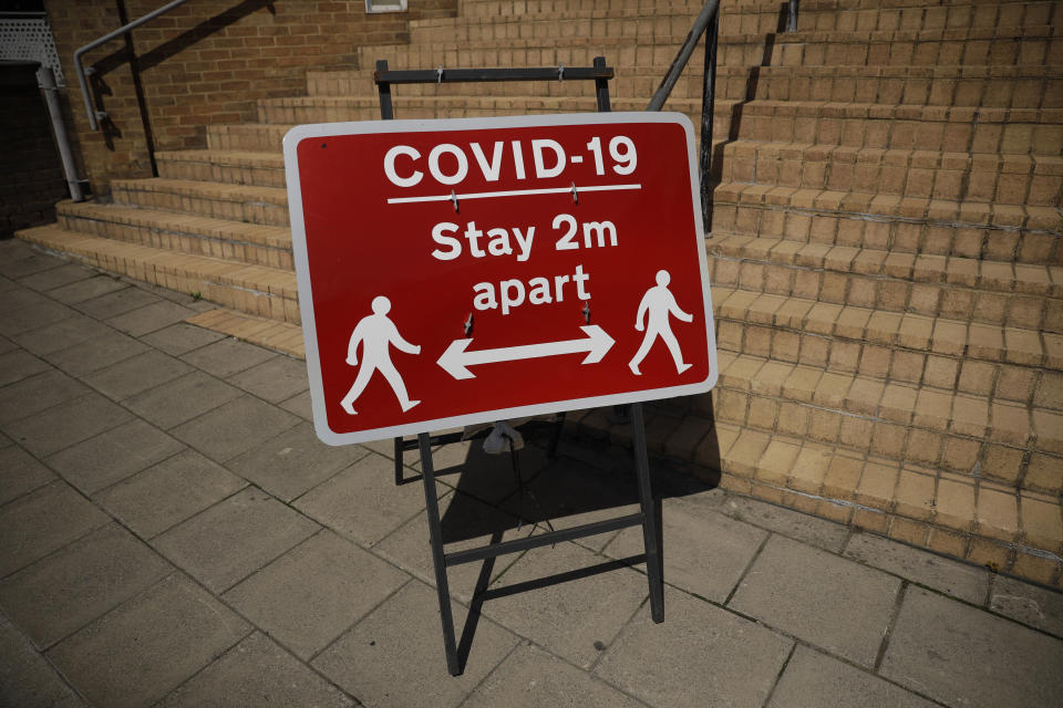 A sign requesting people stay two metres apart is displayed in Kingston upon Thames, south west London, Monday, June 22, 2020. The two-metre social distancing rule will be under review as the UK relax coronavirus lockdown measures implemented to stem the spread of the virus. (AP Photo/Matt Dunham)